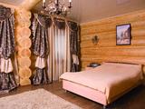 Пышное текстильное оформление и раскидистая металлическая люстра вносят атмосферу роскоши в минималистичный интерьер комнаты.