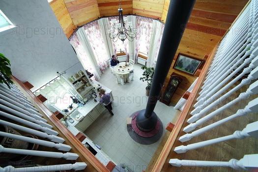 Оттенок древесины контрастирует с белым цветом в отделке некоторых элементов дома, например лестницы и ограждений второго этажа.