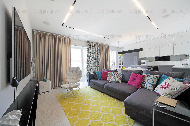 Система освещения гостиной реализована с помощью линейных светильников в потолке