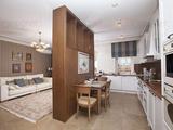 От кухни зона гостиной отделена деревянным стеллажом, выполняющим функцию подставки под телевизор и прочей техники. Рисунок древесины перекликается с лестницей, подчёркивая единство и гармоничность ин