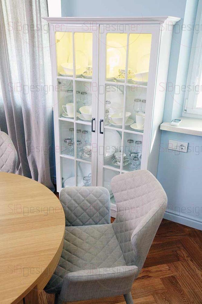 Зону отдыха и кухонную соединяет между собой обеденная группа. Помимо стола и современных мягких стульев композицию дополняет еще и такой классический элемент обстановки, как буфет.