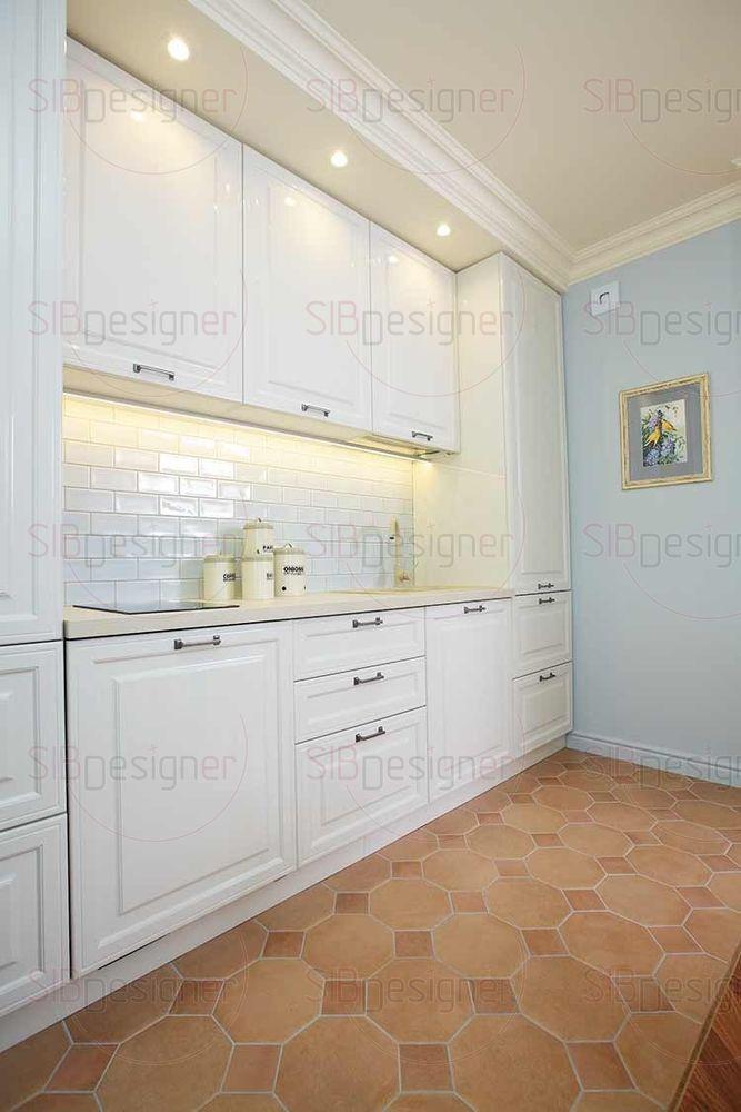Светлые филенчатые фасады кухни выглядят воздушно и легко, фартук отделан керамической плиткой формата кирпича.