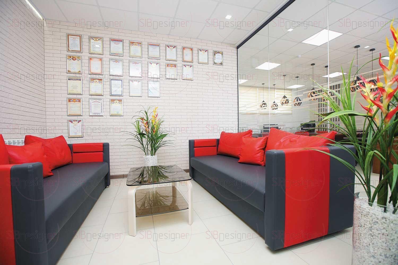 Переговорное помещение украшают стильные яркие диваны на фоне кирпичной стены кремового оттенка.