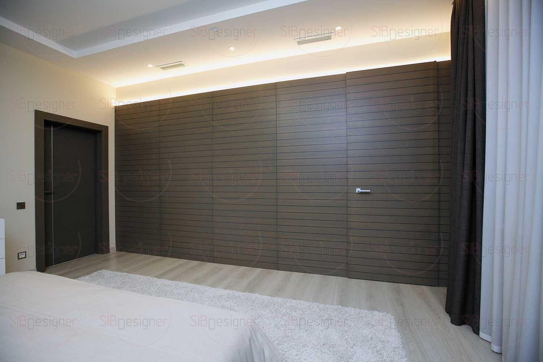 Одна из стен отделана натуральным шпоном, и за ней скрывается вместительная гардеробная. 