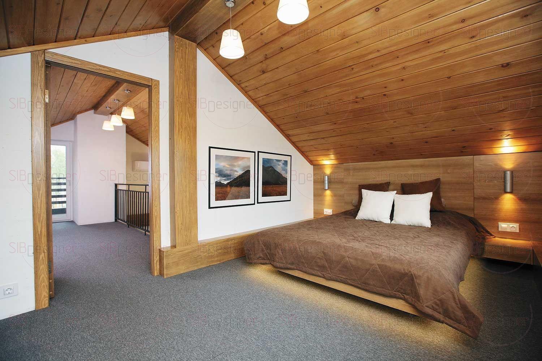 Кровать в спальне на втором этаже поставлена таким образом, чтобы хозяевам не мешал скатный потолок мансарды.