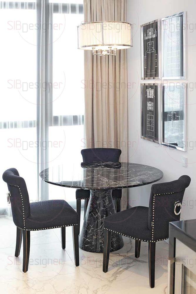 Столовая группа расположилась у панорамного окна. Стол из черного мрамора, мягкие стулья с окантовками в виде декоративных гвоздей.