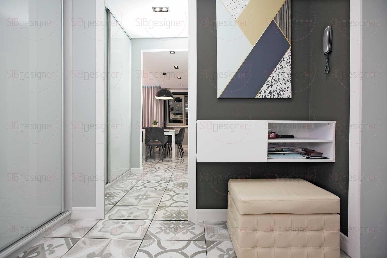 Прихожую можно описать словосочетанием «нарядная практичность»: светло-серая плитка «пэчворк» на полу, огромное зеркало в белой раме.