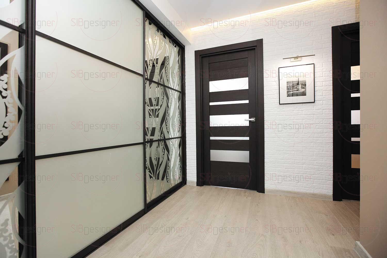 Подобный контраст сохраняется и в прихожей, где к сочетанию рельефной кирпичной и гладкой стен добавляется блеск дверей объемного шкафа-купе.
