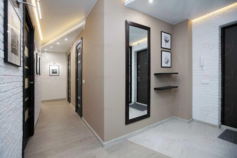 В качестве материала полов почти во всей квартире используется ламинат под светлое дерево.  Одна из стен коридора отделана белым гипсовым кирпичом.