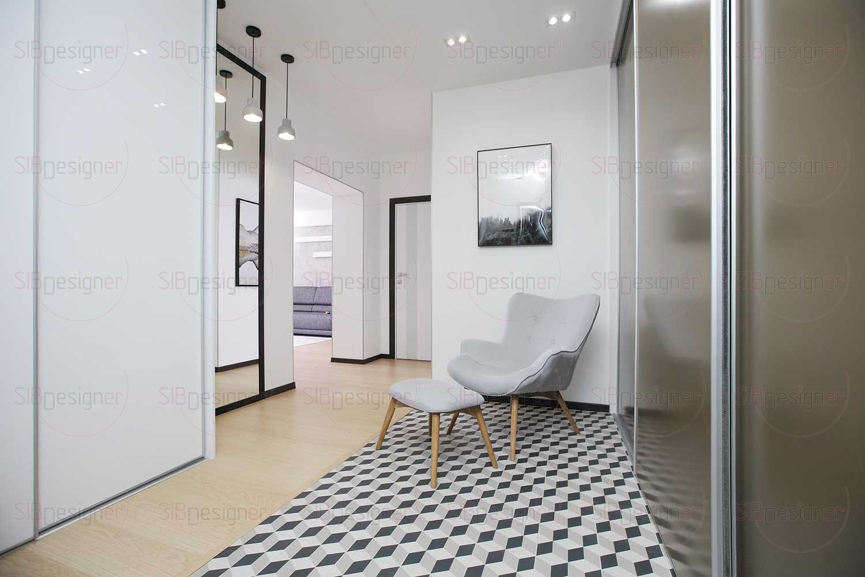 Интерьер прихожей подчеркнуто аскетичен – большую часть пространства занимают шкафы-купе, играющие роль гардеробной, подвесная обувница с полочкой, белое кресло мягких форм и пуф на ножках.