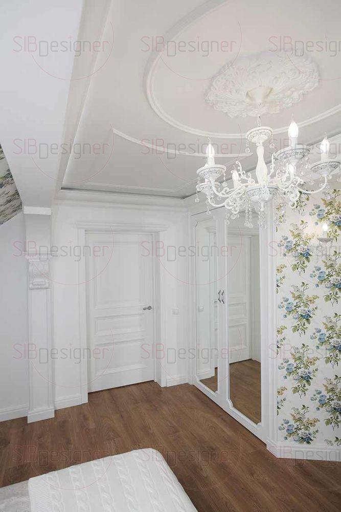 Зеркальные фасады шкафов расширяют пространство спальни, а их белый корпус словно служит продолжением лепного декора, использованного на поверхности стен и потолка.