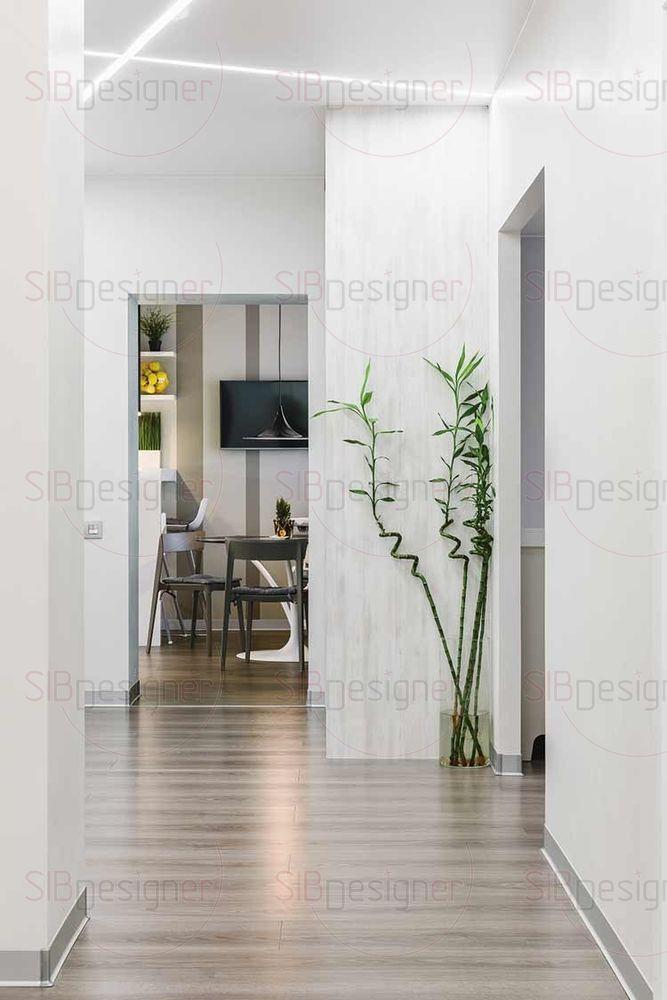 Небольшую по площади прихожую визуально увеличили с помощью обилия белого цвета и встроенных зеркальных шкафов.