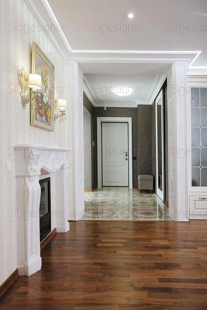 На полу в прихожей и холле интересный керамогранит. В контраст ему стены отделаны темной штукатуркой, в которой угадывается легкий блеск. Вход в гостиную оформлен классической гипсовой лепниной.