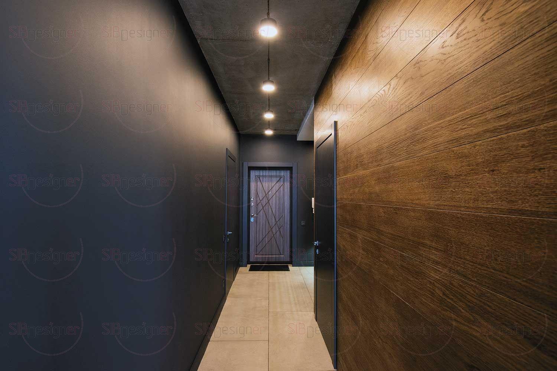 На бетонном потолке коридора светильники открытого монтажа, выстроенные в прямую линию, это еще один элемент стиля лофт.