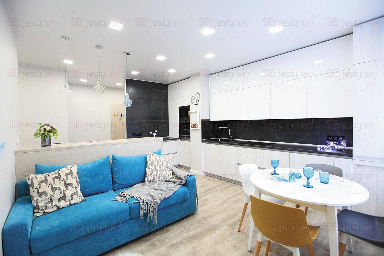 Акцентом в гостиной стал мягкий диван насыщенного лазурного оттенка. Хоть декор в интерьере и сведен к минимуму, противоположную стену от кухни украшает нежная акварельная абстракция.