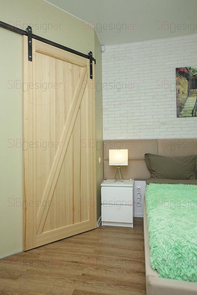 Один из акцентов в спальной комнате – брутальная амбарная дверь из натурального массива сосны