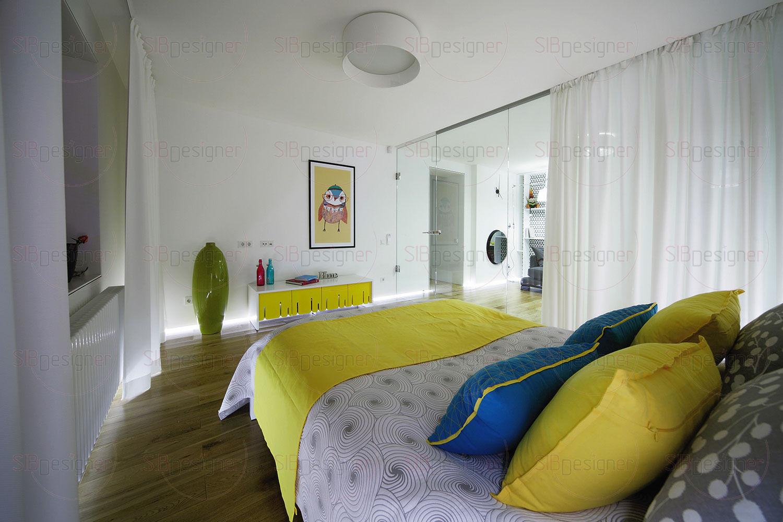 Просторную гостиную разделили стеклянной перегородкой, за которой создали спальную зону для заказчицы